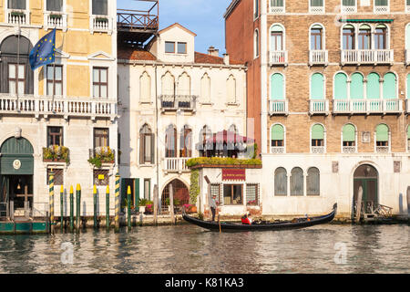 Romantic tour on the Grand Canal in a gondola in evening light, Venice, Italy in front of the Al Ponte Antico hotel - Stock Photo