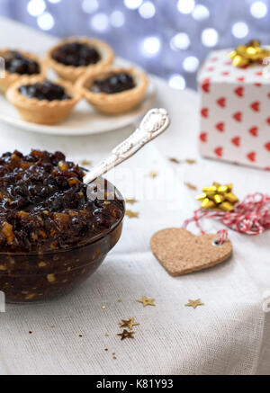 arrangement of homemade traditional Christmas mincemeat  focus on the subject,  with mince pies and bokeh lights - Stock Photo