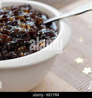 square macro image of homemade traditional Christmas mincemeat made with mixed fruit and brandy in a white bowl, - Stock Photo