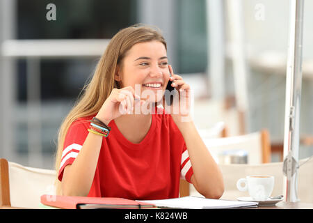 Candid student girl laughing talking on phone siting in a bar terrace - Stock Photo