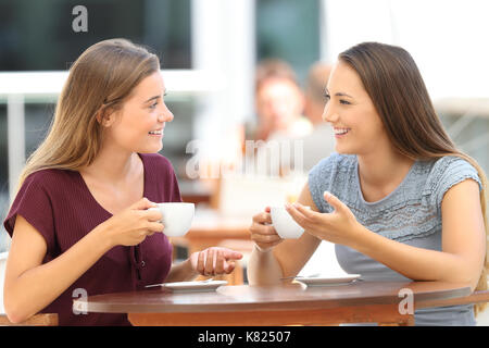 Two happy friends having a good conversation sitting in a bar terrace - Stock Photo