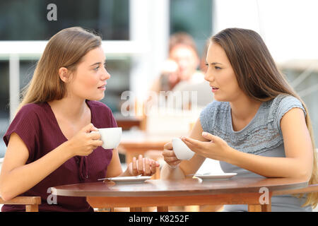 Two serious friends talking sitting in a restaurant - Stock Photo