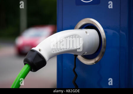 Electric car charging station. Close up of the power supply plugged into an electric car being charged. - Stock Photo