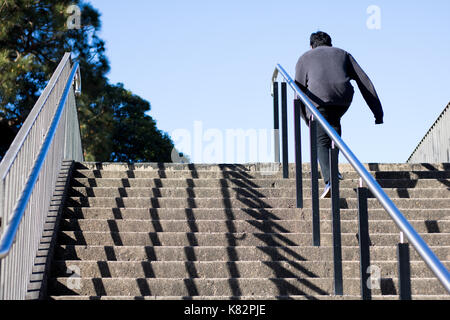 Back view of person climbing stairs - Stock Photo