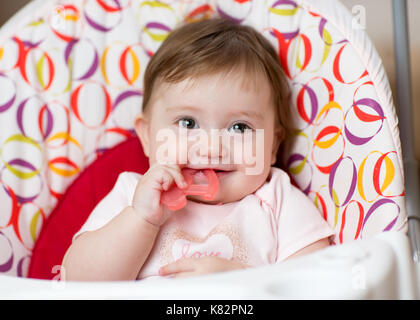 Cute baby chewing on teething toy. First teeth. - Stock Photo