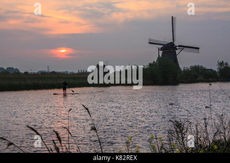 Sunrise on the windmill reflected in the canal Kinderdijk Rotterdam South Holland Netherlands Europe - Stock Photo