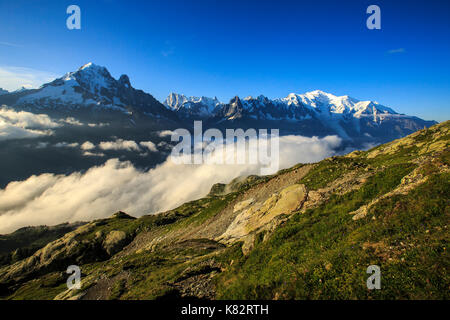 Low clouds and mist frame the snowy peaks of Mont Blanc and Aiguille Verte Chamonix Haute Savoie France Europe - Stock Photo