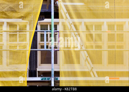 Scaffolding with yellow safety nets during renovation of a building in Rotterdam in the Netherlands - Stock Photo