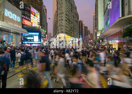Pedestrians and traffic at a busy road crossing in Causeway Bay, Hong Kong Island, Hong Kong, China - Stock Photo