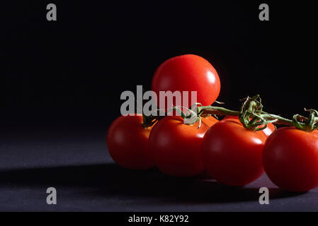 Branch of red organic tomatoes on a black background. - Stock Photo