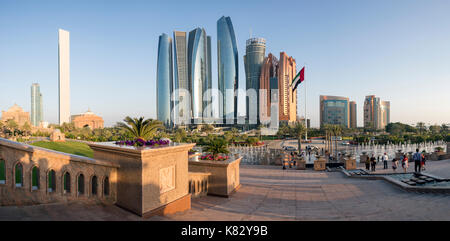 Etihad Towers time lapse viewed over the fountains of the Emirates Palace Hotel, Abu Dhabi, United Arab Emirates, - Stock Photo