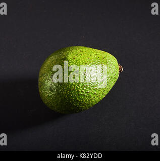 Fresh delicious avocado isolated on a black background - Stock Photo