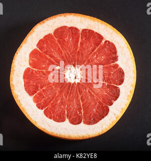 Fresh grapefruit pieces. On black background. - Stock Photo