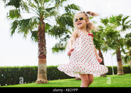 baby girl in a park near trees. - Stock Photo