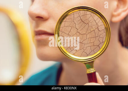 aging and dry face skin concept - woman with magnifying glass - Stock Photo
