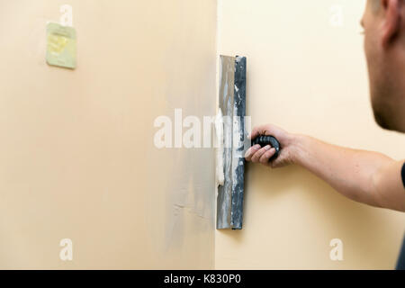 work aligns - worker plastering wall with spatula - Stock Photo