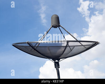 Black satellite dish or TV antennas install on the house roof on blue sky cloudy background. - Stock Photo