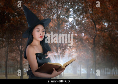 Young asian woman in witches costume holding spell book on the forest - Stock Photo