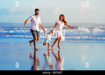 Happy family - father, mother, baby son have fun together, child run with splashes by water pool along sunset sea - Stock Photo