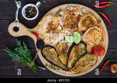 Baked vegetables: eggplant, patisson, tomatoes on a round wooden stand on a dark background. Top view. Vegan dish.