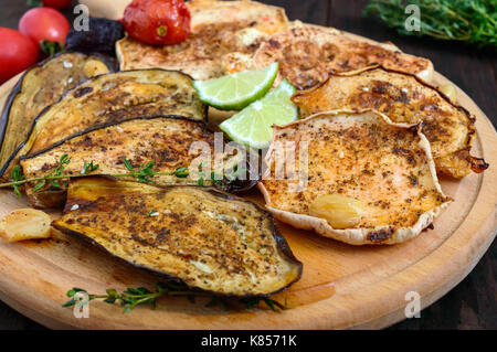 Baked vegetables: eggplant, patisson, tomatoes on a round wooden stand on a dark background.  Vegan dish.