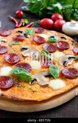 Tasty Italian pizza with salami, mushrooms, mozzarella, basil on a dark wooden table. Top view. - Stock Photo