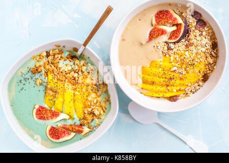 Spirulina and carob smoothie bowls of granola, mango and figs, blue concrete background, vegan healthy breakfast - Stock Photo