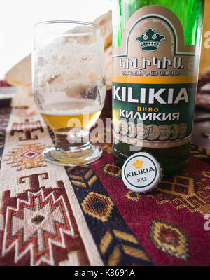 Close up of Armenian Kilikia beer bottle and a near empty glass on a woven  tablecloth with traditional pattern - Stock Photo