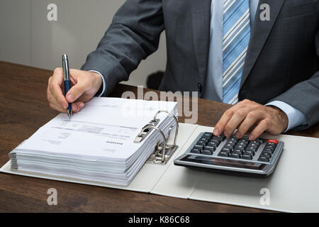 Close-up Of Businessman Calculating Bills With Calculator In Office - Stock Photo