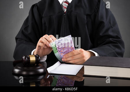 Close-up Of Judge Counting Euro Banknote In Courtroom - Stock Photo