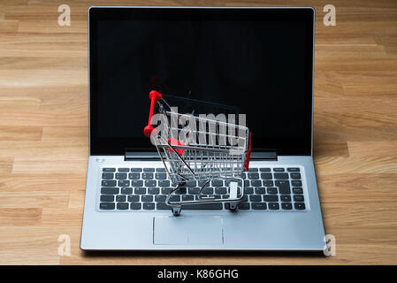 High angle view of shopping cart on laptop at wooden table - Stock Photo
