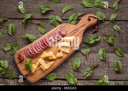 cheese and salami on kitchen board on rustic background. Top view with copy space and herbs . - Stock Photo