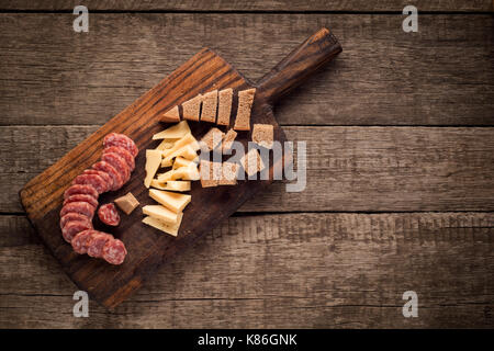 Cutting board with Salami, cheese and bread on dark wooden background - Stock Photo