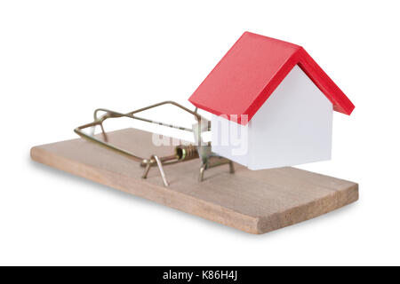 Closeup of house miniature on mousetrap against white background - Stock Photo