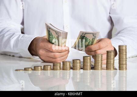 Midsection of businessman counting money at office desk - Stock Photo