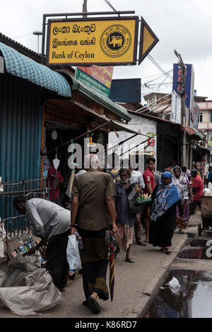 A crowded street scene on a narrow pavement beside the indoor food hall at the Pettah Market in Colombo, Sri Lanka. - Stock Photo
