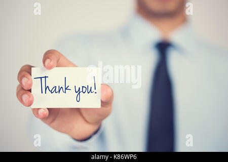 Thank you word on card hold by man - Stock Photo