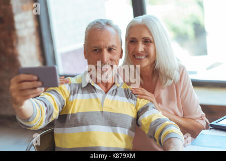 Positive aged couple making selfies - Stock Photo