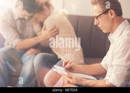 Professional male psychologist taking notes - Stock Photo