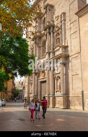 Valencia Spain old town, a group of friends stroll past the baroque entrance of a convent in the old town Barrio - Stock Photo