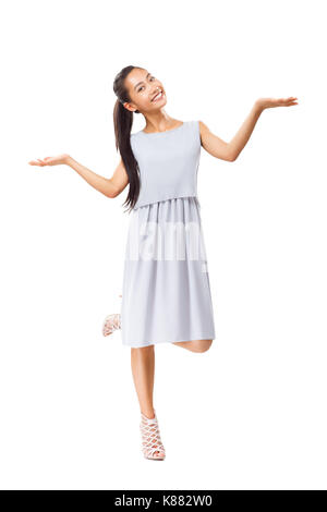 Smiling young Asian woman in grey dress and high heels standing on one leg, showing hand balance and looking at - Stock Photo
