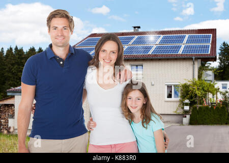 Family Standing In Front House With Solar Panel On Roof - Stock Photo