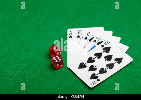 Playing cards flush and red dice on green casino desk  background - Stock Photo
