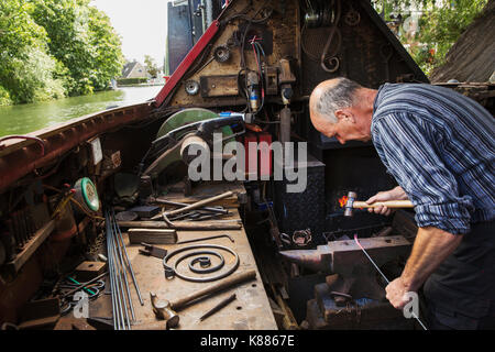 Blacksmith working in a small space on his narrowboat, a barge on river, bending over the anvil and shaping hot - Stock Photo