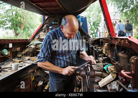Blacksmith standing in his workshop, a floating forge on a narrowboat barge, working on a metal object, using a - Stock Photo