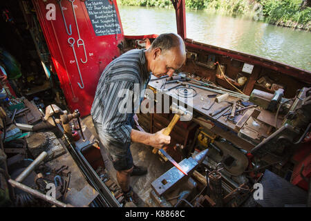 High angle view of blacksmith at his workbench on his working boat on the water, hammering hot metal. - Stock Photo