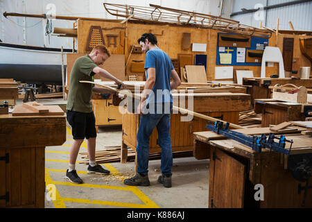 two men in a boat builder s workshop working together on a wooden
