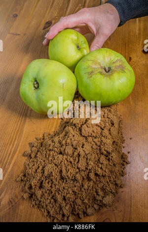 A woman's hand holding one of three raw, Bramley cooking apples, alongside soft brown sugar on a pine kitchen worktop, - Stock Photo