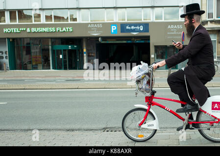 Orthodox Hasidic Jewish man using mobile phone on a bicycle in Antwerp - Stock Photo