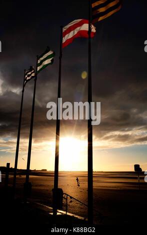 four flags at sunsett on dunkirk beach - Stock Photo